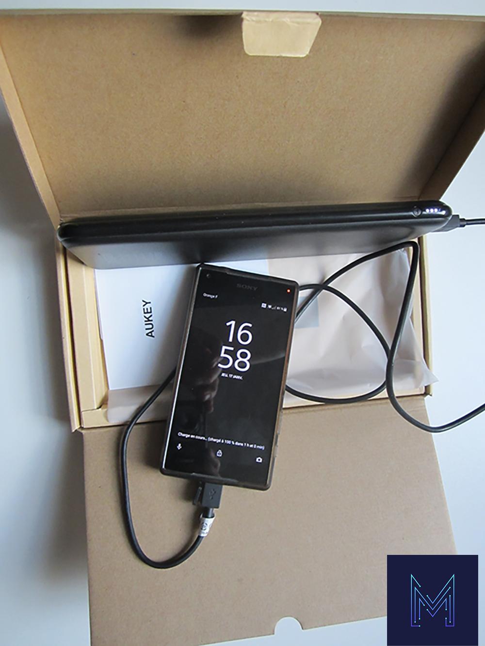 Aukey PB-Y14 dans sa boite et un smartphone branché